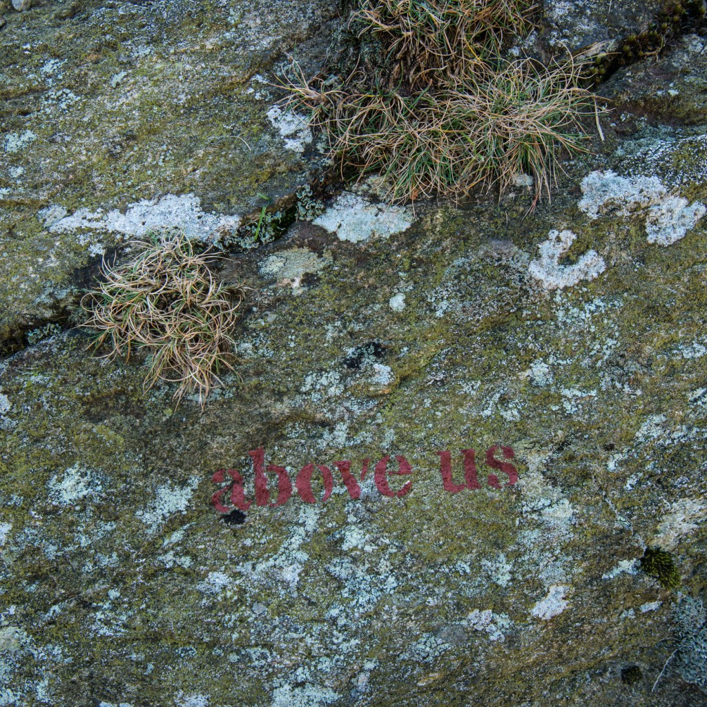 'above us' stencilled on to rock