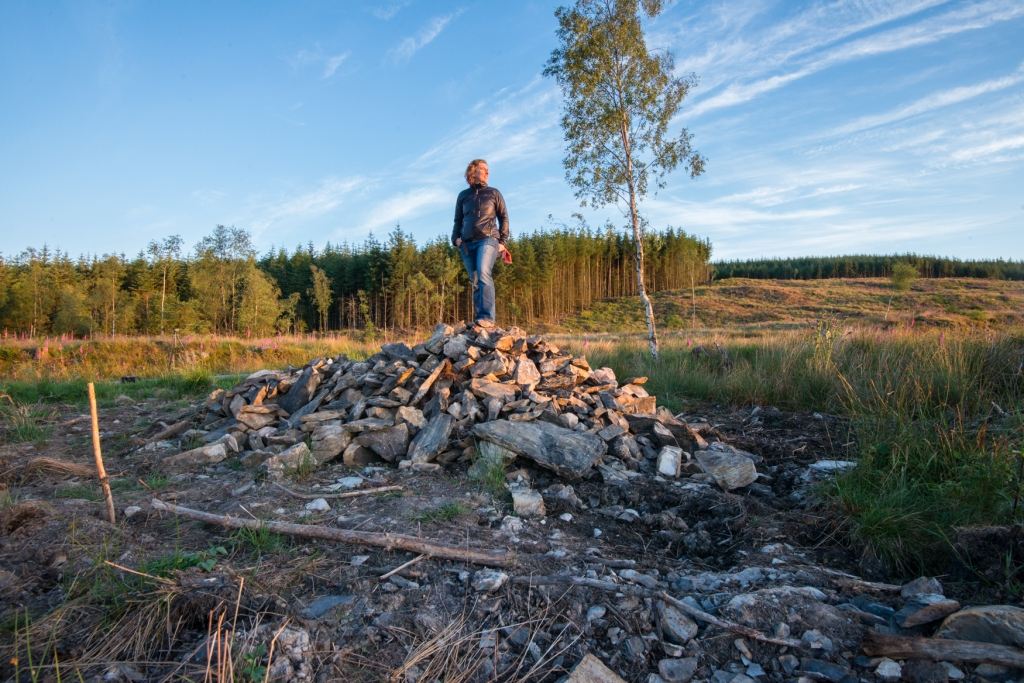 Harriet standing on the pile of stones at the treefold site Grizedale.