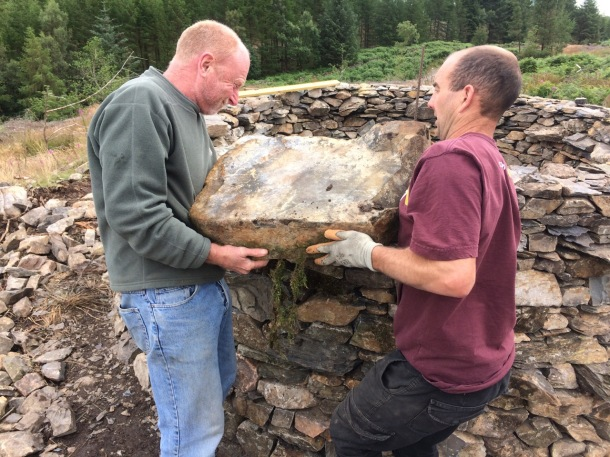 Rob Fraser and Andrew Mason lifting a corner stone at treefold:centre Grizedale